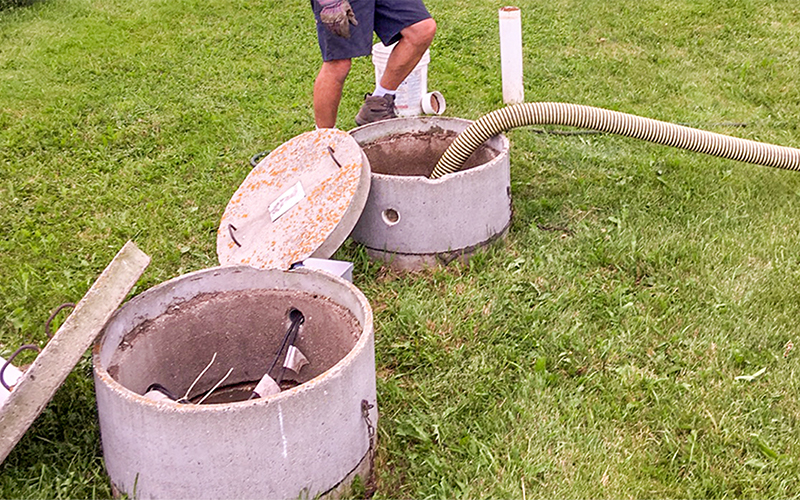 Man pumping out man hole in ground